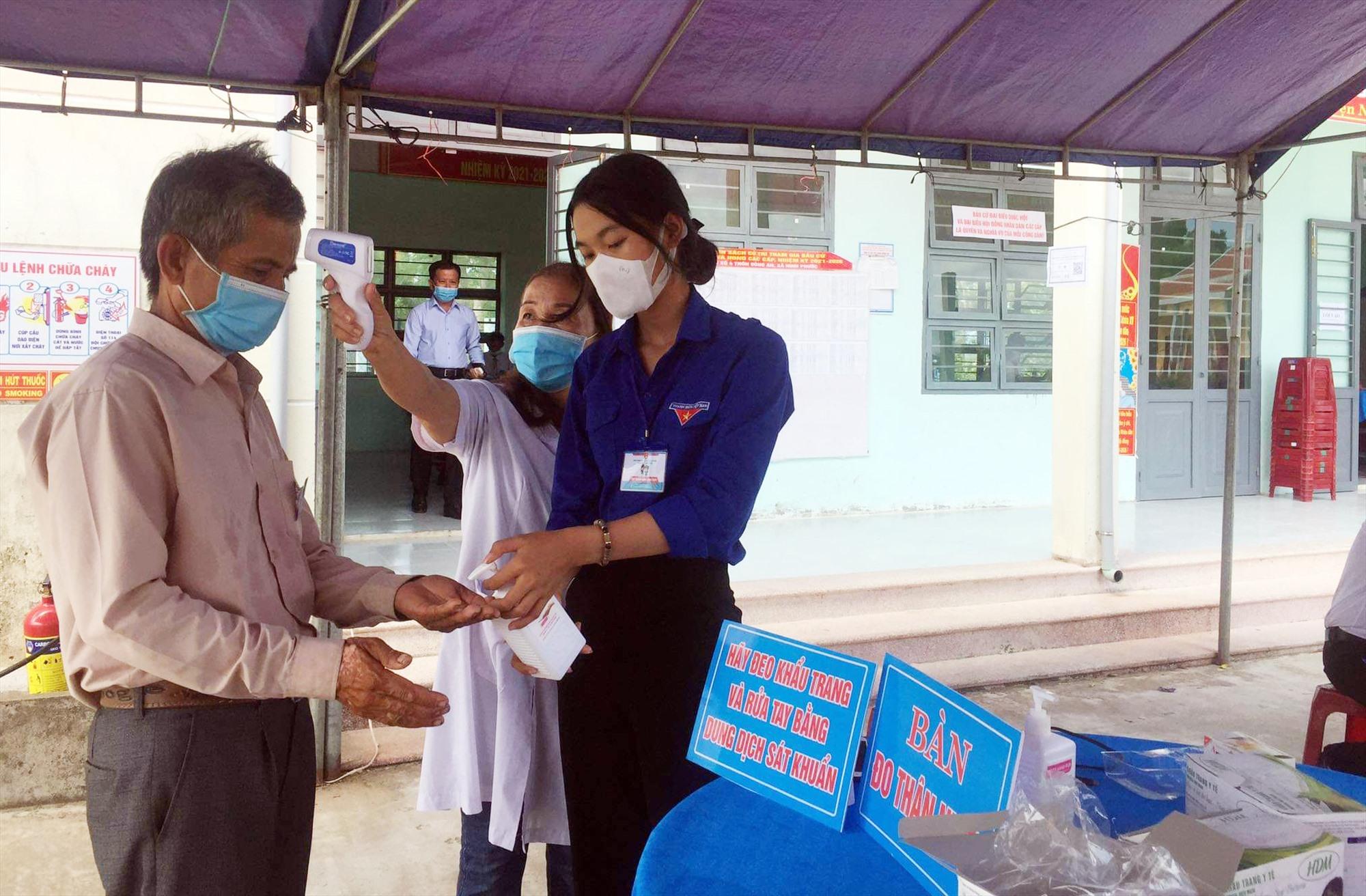 Cử tri Nông Sơn được đo thân nhiệt và rửa tay sát khuẩn trước khi vào bỏ phiếu.
