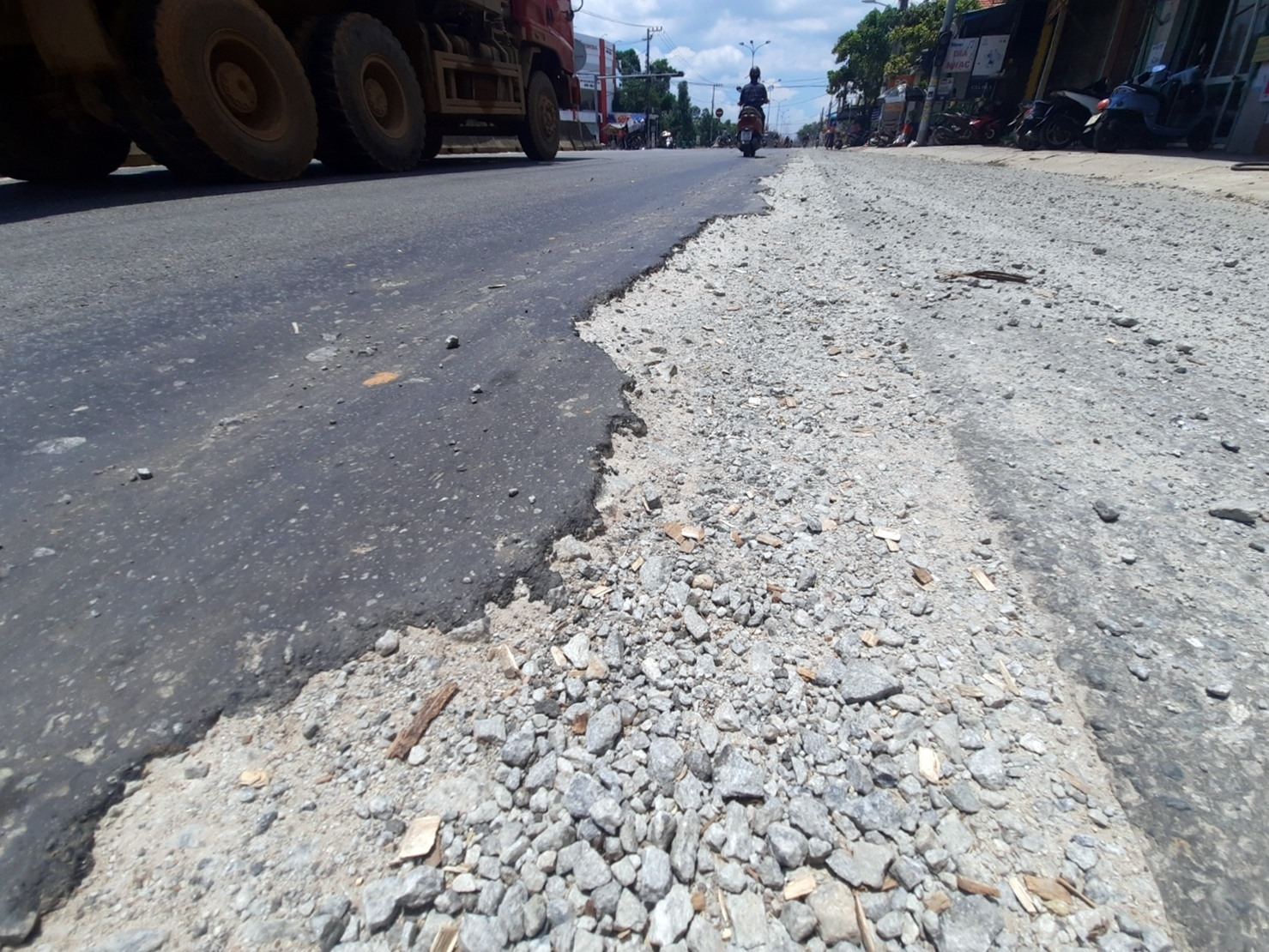 Quốc lộ 1 đoạn qua thị trấn Núi Thành vẫn nham nhở, phần đường dành cho xe máy, xe thô sơ chưa hoàn thiện nên người tham gia giao thông lấn ra phần đường xe ô tô để lưu thông. Ảnh: H.Đ
