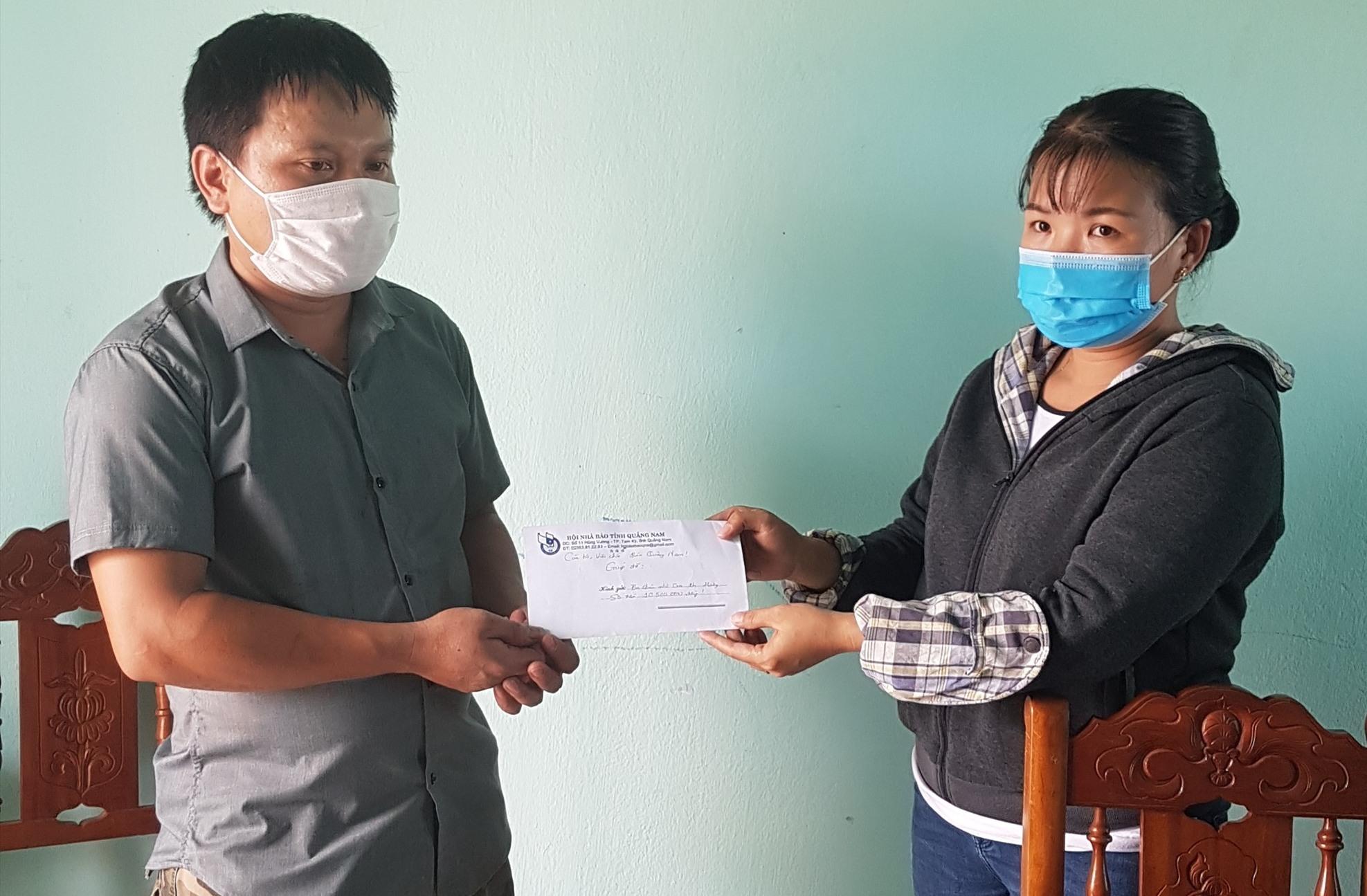 Đại diện Báo Quảng Nam trao tiền hỗ trợ ba cháu nhỏ mồ côi cho đại diện gia đình tại Tổ tiếp nhận cứu trợ xã Tiên Cảnh.