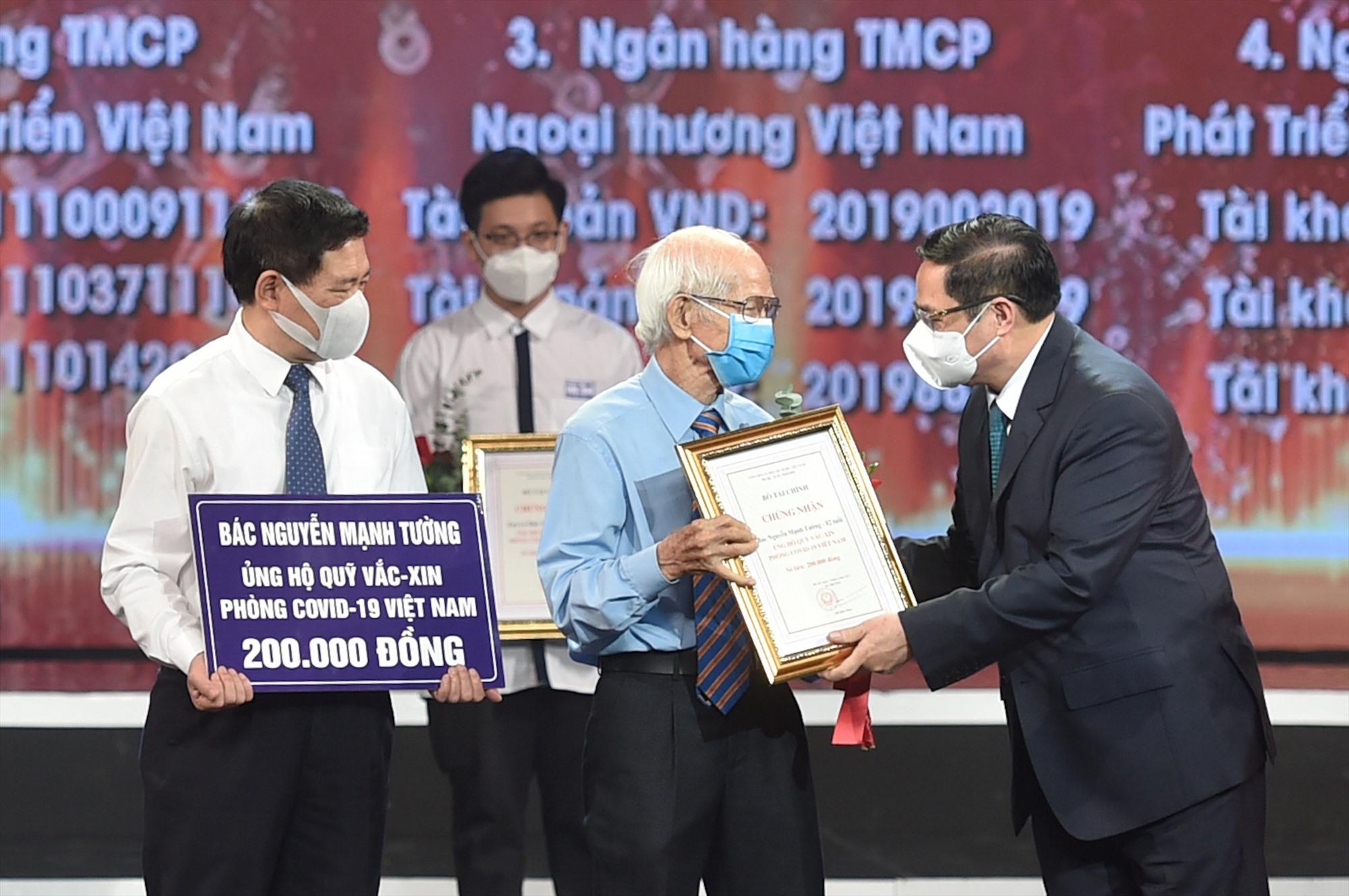 Thủ tướng Chính phủ Phạm Minh Chính trao chứng nhận, hoa cảm ơn bác Nguyễn Mạnh Tường 82 tuổi, cán bộ hưu trí ngành đường sắt. Ảnh VGP