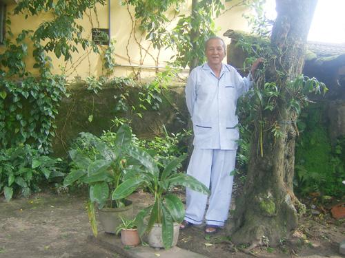Ông Trần Thế Quang bên gốc khế trong sân nhà. Ảnh: QUỐC HẢI