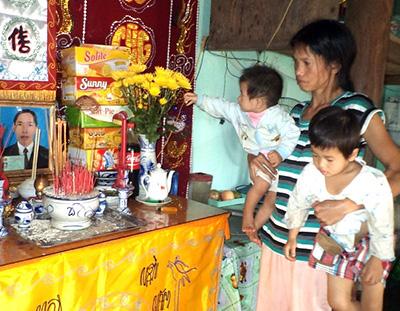 Chị Ngô Thị Thà một nách 2 con nhỏ dại thẫn thờ bên bàn thờ chồng.
