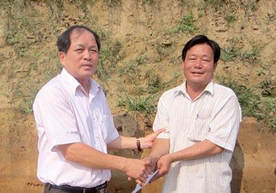 Ông Trương Văn Cận (bên trái) trao tặng 15 triệu đồng cho ông Dũng