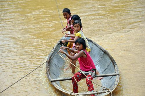 Học sinh trường Tiểu học Zuôih đưa khách qua sông bằng thuyền nhỏ.