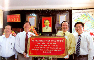 Mr La Trong Thanh, Vice president  of  Tam Ky  FCA in HCMC presenting a Khanh Vang (Gold leaf painting) to the leaders of Tam Ky city People's Committee in the ceremony of 105 years anniversary of founding Tam Ky town.