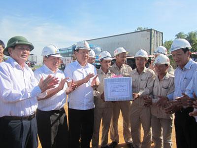Bộ trưởng Đinh La Thăng (thứ 3 từ trái sang) tặng quà động viên công nhân trên công trường.                                                                                                              Ảnh: CÔNG TÚ