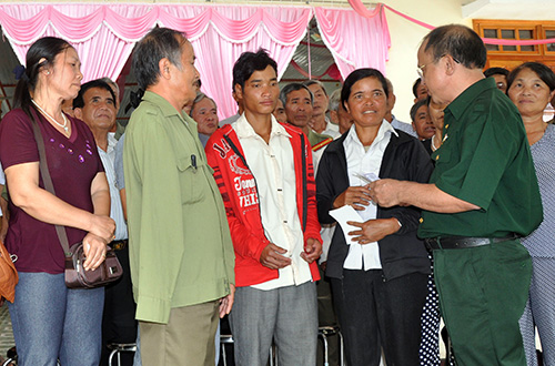 Cựu binh D404 tặng quà cho mẹ con chị Y Niêu nhân cuộc gặp gỡ tại Đắk Pét. Ảnh: HÀN GIANG
