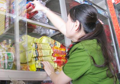 Thành viên đoàn kiểm tra làm việc tại tiệm tạp hóa chị Tuyền (huyện Núi Thành).Ảnh: THỤC ANH