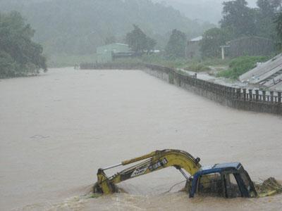 Một xe máy múc tại công trường kè suối chợ thị trấn Trà My bị ngập và lũ cuốn trôi.