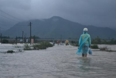 Trên tuyến ĐT611 giữa hai huyện Quế Sơn và Nông Sơn, trong đêm, người dân vẫn tìm cách vượt qua đoạn ngập. Ảnh: TRUNG THÀNH