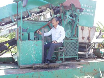 Ông Hồ Văn Luyện đang điều khiển thuyền máy vớt bèo liên hoàn. Ảnh: N.DUY