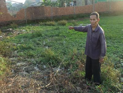 Ông Trung chỉ đám ruộng 400m2 của mình bỏ hoang do ô nhiễm. Ảnh: T.Q