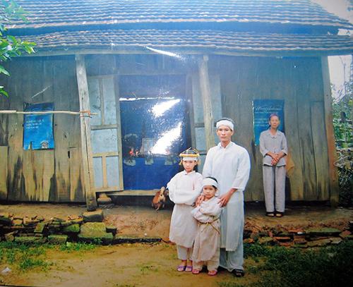 Anh Tám và 2 cháu lớn trước căn nhà của mình.