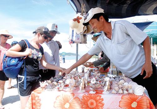 Du khách thích thú tham quan, mua quà lưu niệm tại chợ.Ảnh: MINH HẢI