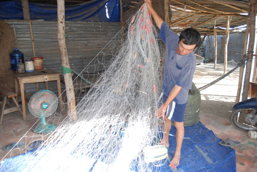 Anh Lê Chí Minh đang kiểm tra lại lưới để sáng mai ra khơi!                                                         ảnh: M.Kiệt