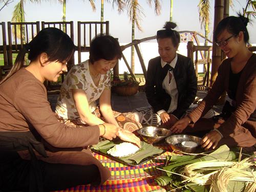 Du khách thích thú khi được trải nghiệm văn hóa tết Việt khi tham gia gói bánh tét.