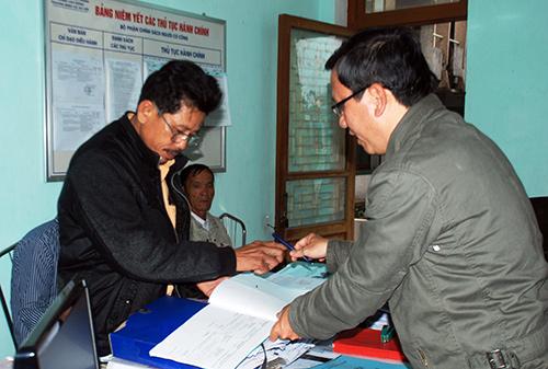 Cán bộ phụ trách công tác người có công ở Phòng LĐ-TB&XH huyện Núi Thành tiếp nhận hồ sơ của công dân. Ảnh: Đoàn Đạo