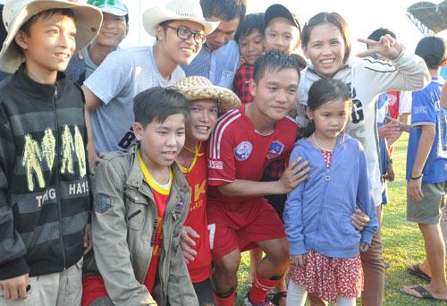 Đinh Thanh Trung trong vòng vây của người hâm mộ đất Quảng sau khi giành quyền thăng hạng ở mùa giải 2013.Ảnh: AN NHI