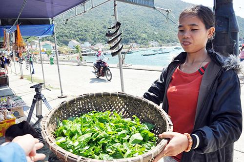 Chị Phạm Thị Tiến với rổ rau rừng mời khách đến đảo. Ảnh: VINH ANH