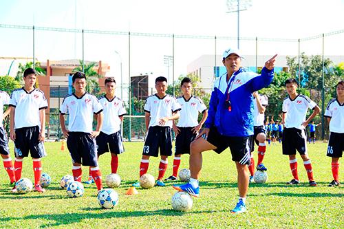 HLV Trần Minh Chiến đang thị phạm cùng các cầu thủ trẻ PVF.