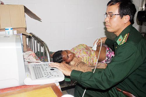 Bác sĩ quân y Huỳnh Văn Ngọc khám bệnh cho chị Avo Hiêm bằng máy siêu âm.