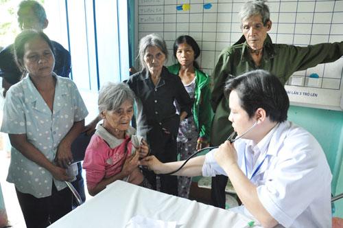 Bác sĩ Dương Chí Lực – Phó Giám đốc Trung tâm Chăm sóc sức khỏe sinh sản Quảng Nam khám bệnh cho người dân. Ảnh: VINH ANH