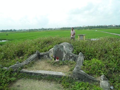 Ông Trần Văn Hà bên ngôi mộ thương gia Tani Yajirobei ngay giữa cánh đồng làng.