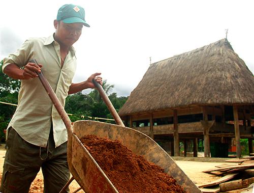 Bí thư Chi bộ thôn Tà Vàng (xã A Tiêng, Tây Giang) Zơ Râm Chôi kéo đất gia cố móng nhà cho người dân.Ảnh: HÀN GIANG