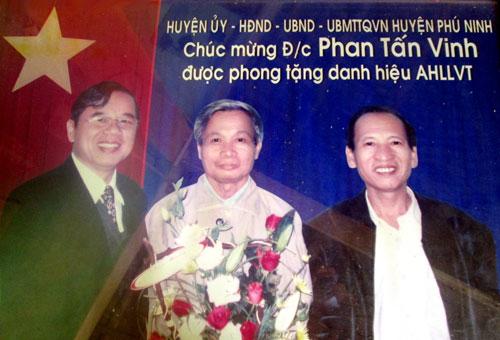 Lãnh đạo huyện Phú Ninh tặng hoa chúc mừng đồng chí Phan Tấn Vinh (giữa) được phong tặng danh hiệu Anh hùng lực lượng vũ trang nhân dân.