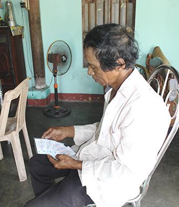 Ông Nguyễn Hữu Dũng vừa nhận thẻ BHYT năm 2014 của cả nhà từ đại lý thu. Ảnh: D.LỆ