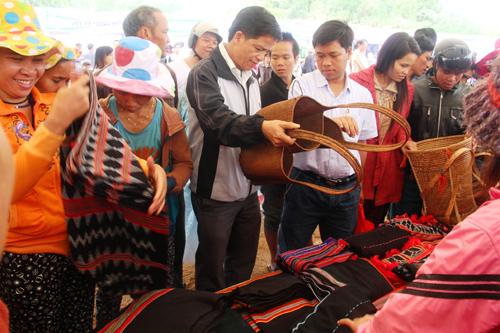 Du khách tham quan, mua sắm các mặt hàng truyền thống của đồng bào Cơ Tu. Ảnh: LĂNG A CÚI