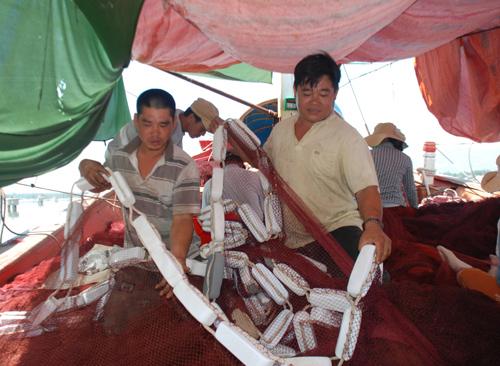 Đảng viên Huỳnh Ngọc Tuấn (bên phải) cùng các bạn tàu chuẩn bị ngư cụ vươn khơi ngư trường Hoàng Sa. Ảnh: ĐOÀN ĐẠO