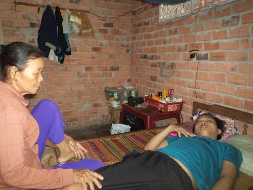 Bà Hoa hàng ngày chăm sóc đứa con trai bất hạnh của mình. Ảnh: A.V