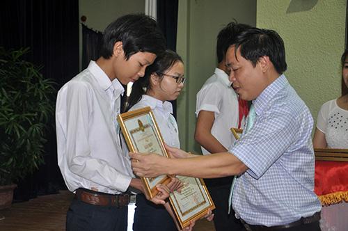 Phó Chủ tịch UBND TP.Tam Kỳ Bùi Ngọc Ảnh tặng giấy khen và tiền thưởng của thành phố cho các em học sinh đoạt giải