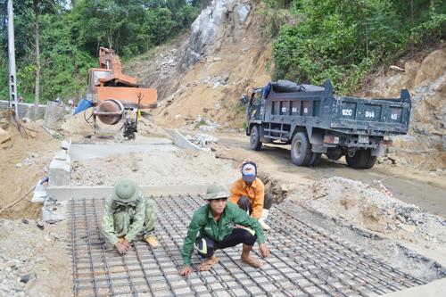 Công nhân Công ty CP Công trình GTVT Quảng Nam sửa chữa, khắc phục hậu quả lũ lụt trên tuyến ĐT611. Ảnh: CÔNG TÚ