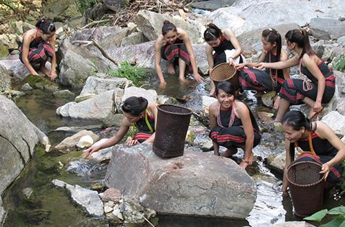 Thiếu nữ Ca Dong ra suối bắt ốc đá, lấy vỏ làm vôi trộn với thuốc để ăn.