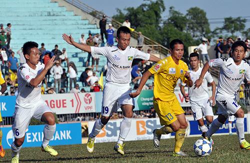 Nguyễn Văn Vinh (áo vàng) trong vòng vây của các cầu thủ Sông Lam Nghệ An