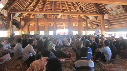 Cán bộ, những người con quê hương A Xan tập hợp tại gươl  làng trao đổi, đóng góp tạo Quỹ khuyến học cộng đồng. Ảnh: HOÀNG YÊN