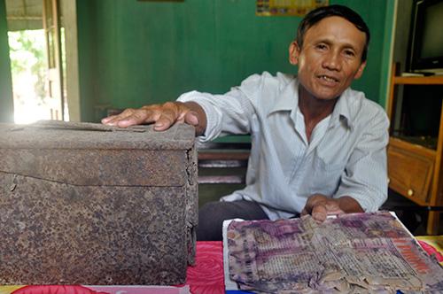Ông Huỳnh Kim Phiến nói về các kỷ vật của cha cất giấu trong thùng đạn chôn dưới địa đạo Kỳ Anh. Ảnh: HÀN GIANG