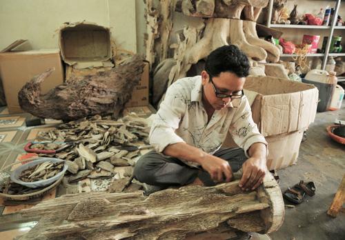 Nghệ nhân làng trầm Trung Phước đang tạo dáng cho cây trầm cảnh.Ảnh: V.C.L
