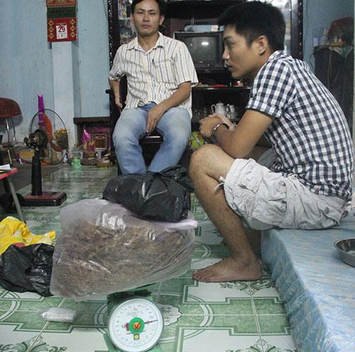 Đối tượng Nguyễn Thanh Hùng áo rô đen (bên phải) cùng tang vật bị bắt giữ tối 15.7.