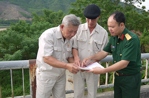 Cựu chiến binh Trung đoàn 31 dựa vào sơ đồ trận đánh Nông Sơn năm xưa để xác định các vị trí đã từng chiến đấu.  Ảnh: HỒNG VÂN