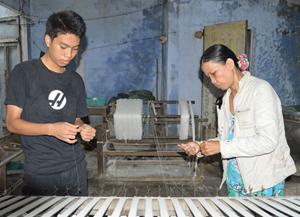 Nguyễn Duy Sơn giúp mẹ xe sợi lúc rảnh rỗi.ảnh: V.LỘC