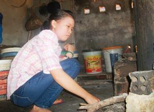 Đoàn Thị Thu Hà phụ gia đình việc bếp núc và chăn nuôi heo.  ảnh: V.H