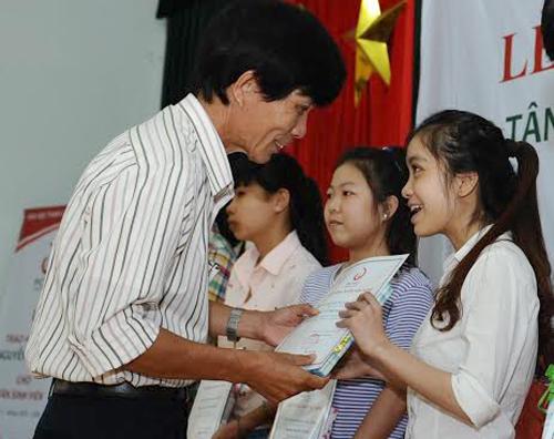 Ông Nguyễn Sự - Bí thư Thành ủy Hội An trao học bổng Nguyễn Thị Bình cho các tân sinh viên.
