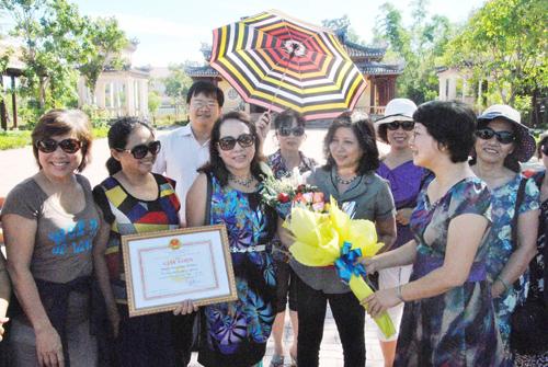 Lãnh đạo phòng VH-TT thành phố tặng hoa chúc mừng những du khách đầu tiên đến tham quan Văn thánh Khổng miếu.Ảnh: N.Đ.N