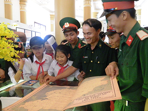 Soldiers and teenagers watching the maps and documents on Vietnam's sovereignty over the Hoang Sa and Truong Sa archipelagos.