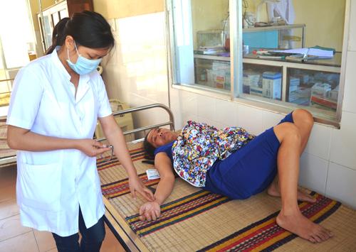 Y sĩ Phạm Thị Dung đang chăm sóc người bệnh ở Bệnh xá quân dân y kết hợp xã đảo Tân Hiệp. Ảnh: N.Q.V