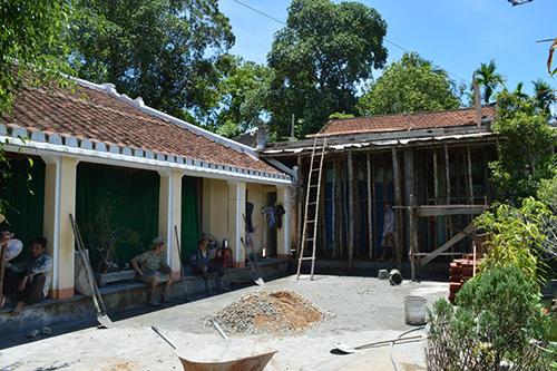 Kề bên ngôi nhà cổ của cụ Nguyễn Huỳnh Anh là một ngôi nhà đang được đổ bê tông.