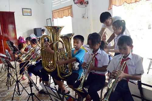 Học sinh tiểu học tiếp cận với các nhạc cụ hiện đại do KOICA tài trợ. Ảnh: VĨNH LỘC